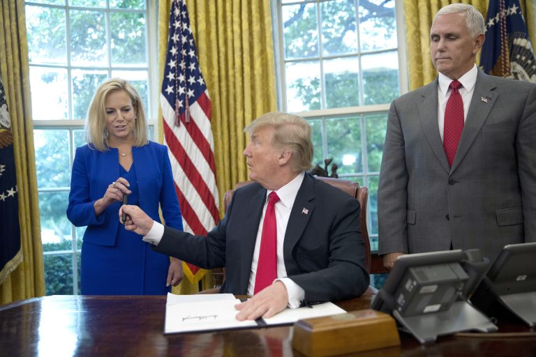 In this June 20, 2018, photo, President Donald Trump gives the pen he used to sign the executive order to end family separations at the border to Homeland Security Secretary Kirstjen Nielsen, (left), as Vice President Mike Pence, (right), watches in the Oval Office of the White House in Washington. Nielsen has one hard-earned presidential signing pen, receiving hers after Trump used it to sign the executive order. By the time Trump reversed his policy Wednesday, Nielsen had been both yelled at and praised by Trump and pilloried for repeating his falsehoods.  (Pablo Martinez Monsivais/AP Photo)