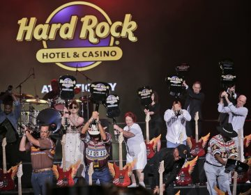 Celebrities and VIPs smash guitars as part of the grand opening celebration at the Hard Rock Hotel and Casino in Atlantic City Thursday. Movie stars lent an air of celebrity glitz to the gritty seaside gambling resort as two of its shuttered casinos reopened with more than 6,000 of the 11,000 jobs it lost during a brutal stretch of casino shutdowns. (Seth Wenig/AP Photo)