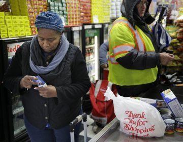 A woman organizes her pocketbook after paying for groceries with an EBT card (Seth Wenig/AP Photo)
