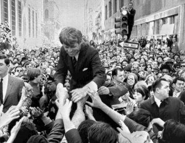 In this April 2, 1968 file photo U.S. Sen. Robert F. Kennedy, D-NY, shakes hands with people in a crowd while campaigning for the Democratic party's presidential nomination on a street corner, in Philadelphia. (Warren Winterbottom/AP Photo, File)