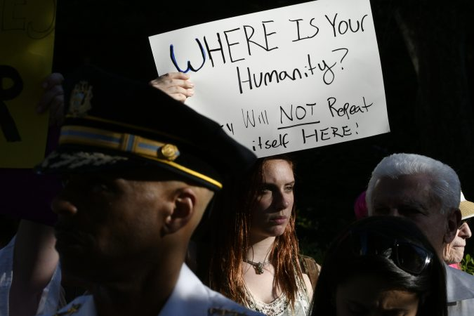 Protester holding a sign during Vice President Mike Pence's visit to Philadelphia. June 19. 2018. (Bastiaan Slabbers for WHYY)