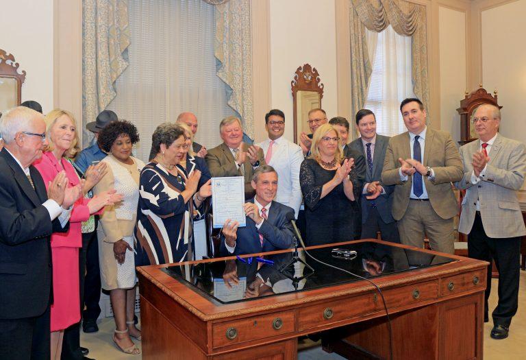 Delaware Gov. John Carney signs legislation banning bump stock devices Thursday. (Courtesy of Jen Rini)