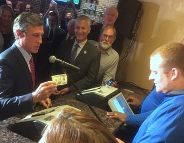Gov. John Carney, D-Delaware, places a $10 bet on the Phillies. (Zoe Read/WHYY)