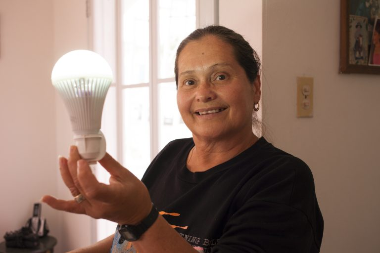 Minerva Ortolaza holds a rechargeable bulb her sister, Santa, uses to light her house. The Ortolazas didn't have light for months after Hurricane Maria hit Puerto Rico and they had to change their routines to make do. (Irina Zhorov/WHYY)