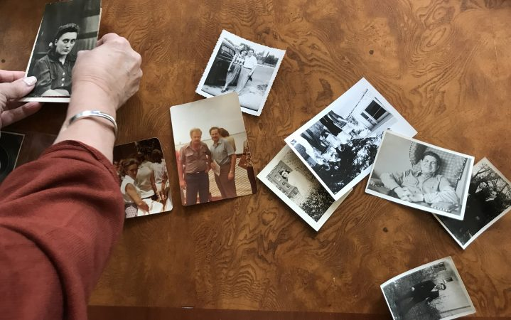 Judy Eidelson lays out pictures of her family members, some of whom died during the Holocaust. (Laura Benshoff/WHYY)