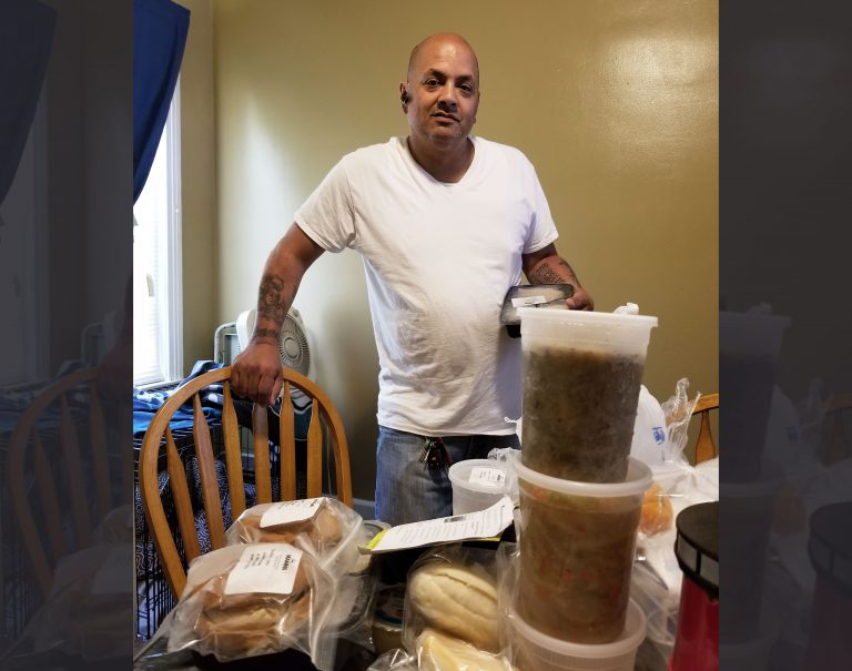 Feliciano Pagan, a Medicaid recipient in Philadelphia, looks over his medically tailored meals made at the kitchens of the nonprofit MANNA and paid for by Health Partners Plans, his Medicaid health plan.