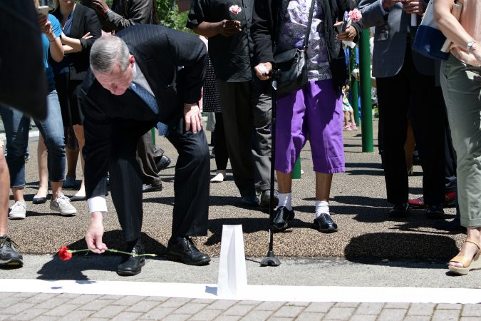 Major Jim Kenney, community members and elected officials place flowers on a symbolic border after the Philadelphia officially announces the development of Bethel Burying Ground Historic Site Memorial during a ceremony at Weccacoe Playground, in South Philadelphia, on Tuesday June 12, 2018. (Bastiaan Slabbers for WHYY)