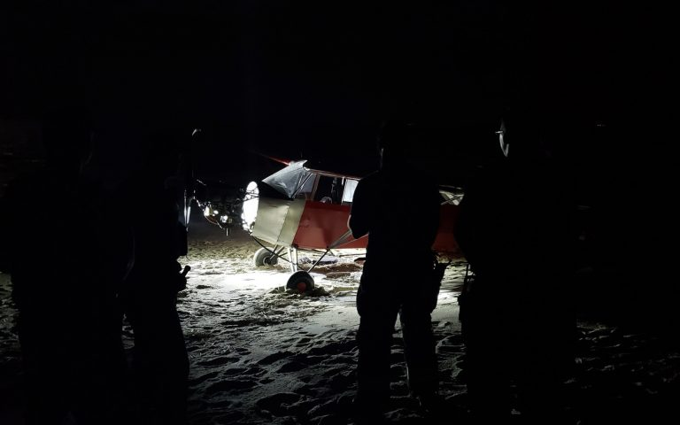 In this June 24, 2018 photo, Coast Guard personnel stand in front of a plane on a secured beach on the southeast side of the U.S. Coast Guard Training Center Cape May after it landed illegally and there was no sign of the pilot. The Coast Guard says officers became aware of the incident when the plane was spotted on closed-circuit cameras. (Petty Officer 2nd Class Richard/U.S. Coast Guard via AP)