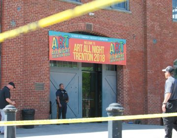 A police officer stands guard outside of the Historic Roebling Wire Works building on S. Clinton Avenue in Trenton, N.J. following a shooting at an all-night arts festival being held there. (Natalie Piserchio for WHYY)
