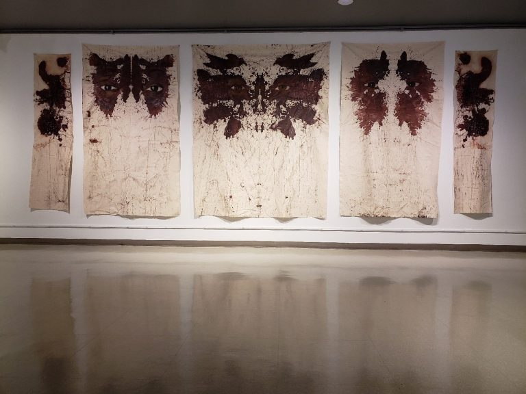 Russell Craig's wall-sized paintings resemble Rorschach tests, with the faces of women killed by police peering out from inside the abstract shapes. His work is on display in a group show at the African American Museum in Philadelphia. (Image courtesy of the African American Museum in Philadelphia)