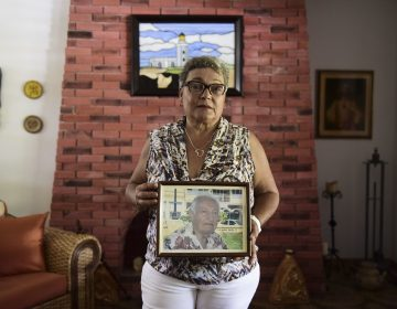 Puerto Rican Nerybelle Perez poses with a portrait of her father, World War II veteran Efrain Perez, who died after his ambulance was turned away from the island's largest public hospital when it had no electricity or water following Hurricane Maria. (Carlos Giusti/AP)