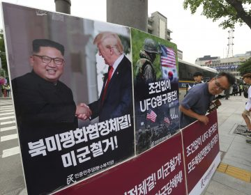 A photo of President Trump and North Korean leader Kim Jong Un is on display as a member of People's Democratic Party stands in opposition of military exercises between the United States and South Korea near the U.S. embassy in Seoul on Tuesday. (Ahn Young-joon/AP)