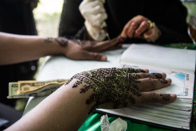 A woman recieves a henna tattoo at an Eid al-Fitr celebration, marking the end of Ramadan. (Kimberly Paynter/WHYY)