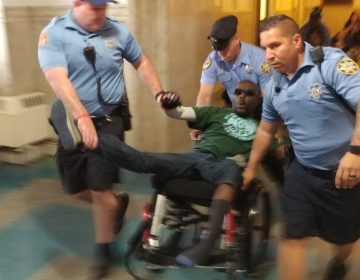 Philadelphia sheriff's deputies eject a protester from City Council chambers Thursday after he and others staged a die-in to protest a lack of housing for those with disabilities. (Tom MacDonald/WHYY)