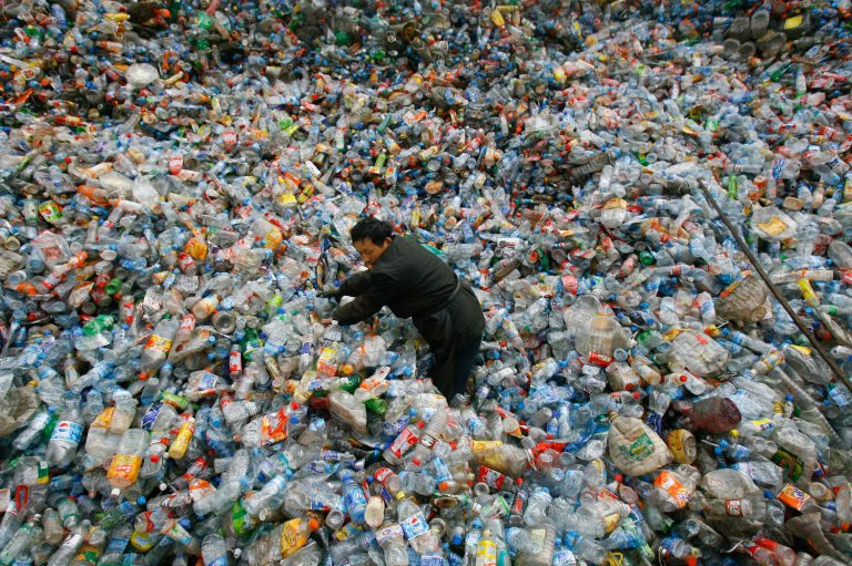 A worker sorts plastic bottles at a recycling center in China. (Jie Zhao/Corbis via Getty Images)