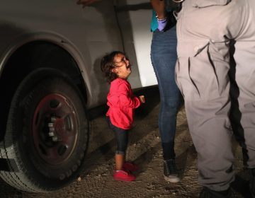 A 2-year-old Honduran asylum seeker cries as her mother is searched and detained near the U.S.-Mexico border on June 12 in McAllen, Texas. The asylum seekers had rafted across the Rio Grande River from Mexico and were detained by U.S. Border Patrol agents before being sent to a processing center for possible separation. (John Moore/Getty images)