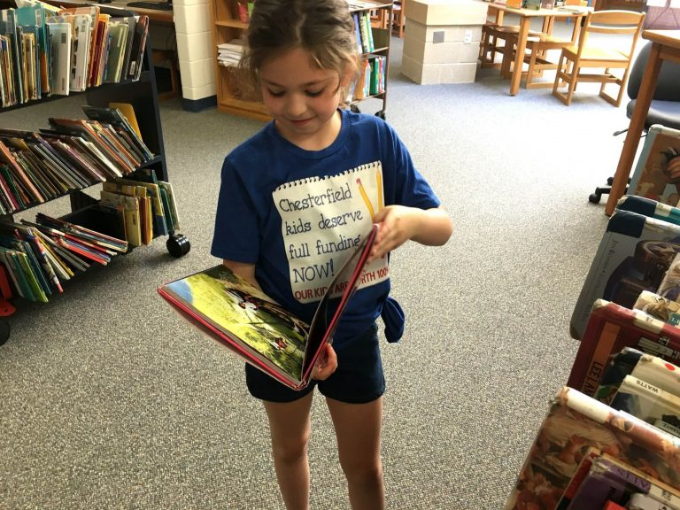 A Chesterfield student peruses a graphic novel in the school library, which officials say doesn't have enough money for books. (Karen Rouse for WHYY News)