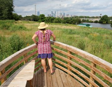 Environmental artist Stacy Levy looks toward the Schuylkill River from the prow of one of her boatlike