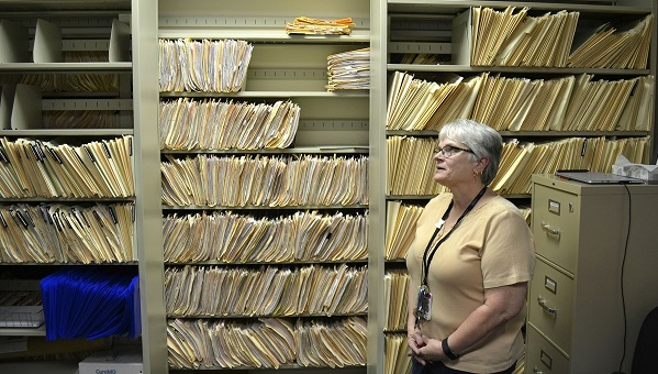 Environmental risk inspector Marilou Yingling stands in front of years worth of files related to lead found in York homes. (Brett Sholtis/Transforming Health)
