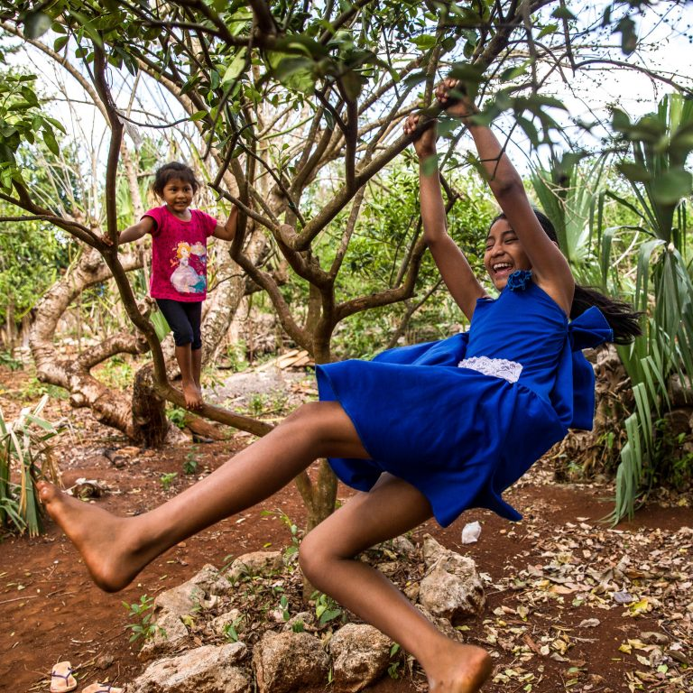 Gelmy, 9, and sister Alexa, 4, climbing trees in the backyard of their family home in the Yucatan Peninsula. (Adriana Zehbrauskas for NPR)