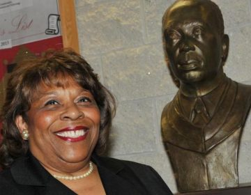 Wilma Mishoe has been named the first permanent female president of Delaware State University. She has been interim president since January. The bust next to her is of her father Luna, who was the school's president from 1960 to 1987.