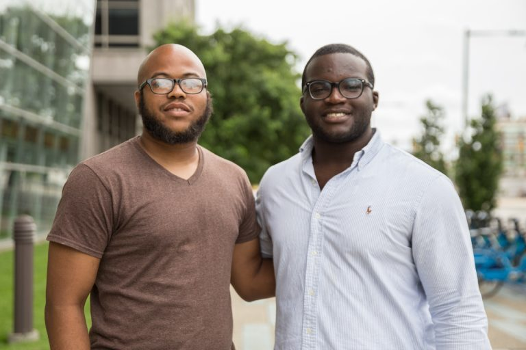 Farrad McLaughlin, (left), and Chris Felix, (right), are scholars from Philadelphia Futures, a program that helps first generation college students graduate. McLaughlin just earned his Master's Degree from Cabrini University and Felix just graduated cum laude from Lafayette College. (Lindsay Lazarski/WHYY)