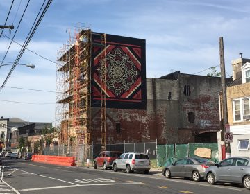 Scaffolding surrounds the proposed site of a Fishtown hotel, next to Frankford Hall. The sidewalk has been blocked off for years. A Shepard Fairey mural is painted on the side of the building. (Mark Dent)