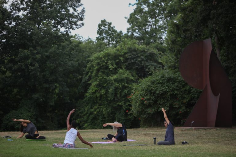 Locals gather in in the Copeland Sculpture Garden at the Delaware Art Museum for some morning yoga. (Emily Cohen for WHYY)