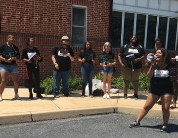 Outside the board of governors meeting, a small group of students rallied for, among other things, free higher education. (Katie Meyer/WITF)