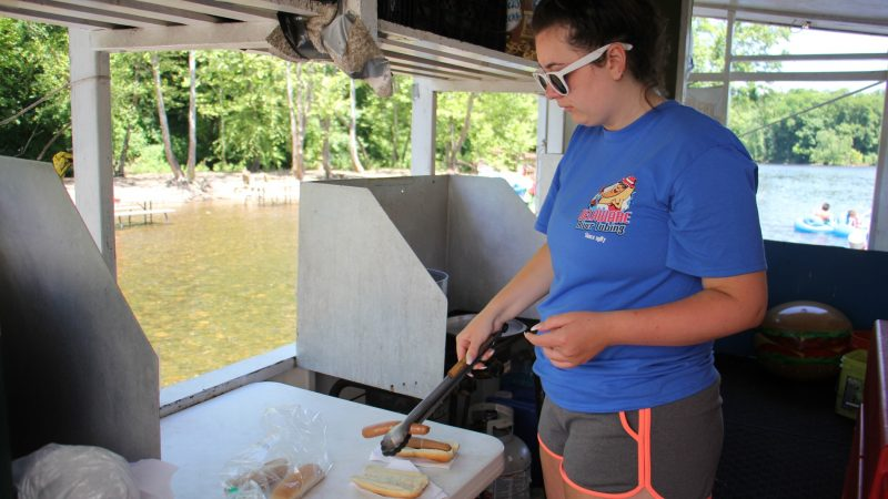 Amanda Nepton serves up some boiled hot dogs to customers who must wade up to the window. (Emma Lee/WHYY)