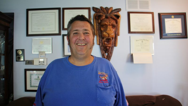 Greg Crance, the founder of The Famous River Hot Dog Man stands in his home office in Southampton. All four of his sons help to run the family business and have either completed their master's degrees or are working toward them. Their diplomas decorate the walls of his office. (Emma Lee/WHYY)