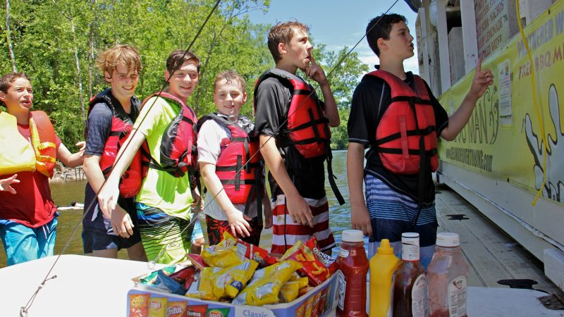 Jacob Tannenbaum (right), celebrating his 13th birthday with a tubing party, places his order at the Famous River Hot Dog Man. (Emma Lee/WHYY)