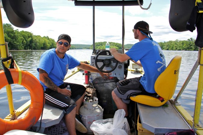 Mathew Crance and boat driver Nash Hughes head downriver toward the hot dog stand, loaded with tools and supplies. (Emma Lee/WHYY)