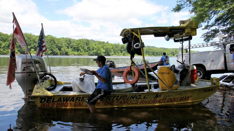 Mathew Crance loads a boat with supplies and heads to the hot dog stand, docked in the Delaware River off Adventure Island, which is owned by the Crance family. (Emma Lee/WHYY)