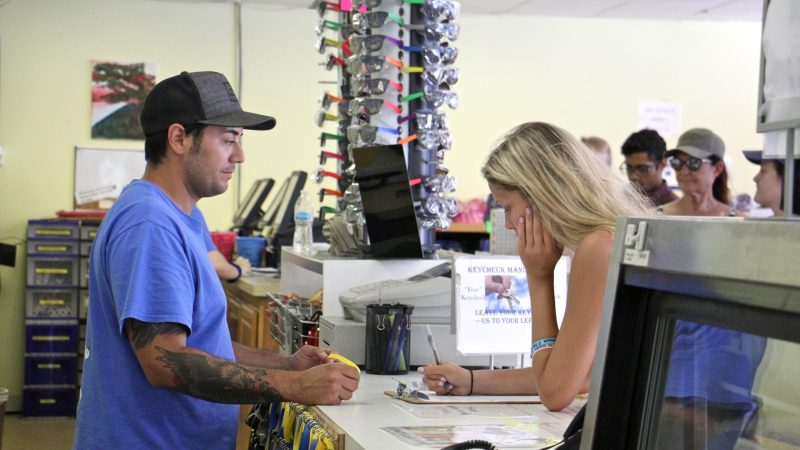 Mathew Crance checks in customers at Delaware River Tubing in Milford. Leaving the office with little more than a life jacket and a bottle of sunscreen, the tubers will be picked up down river four to six hours later. (Emma Lee/WHYY)