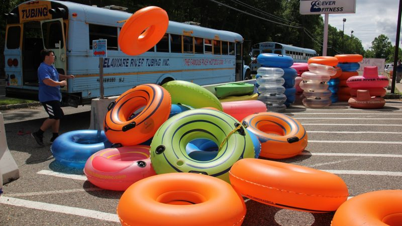 As the day begins at Delaware River Tubing, an employee unloads a bus full of tubes. (Emma Lee/WHYY)