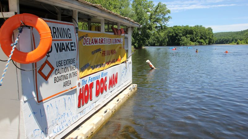 Tubers on the Delaware River approach the Famous River Hot Dog Man. Nearly all stop for a bite and a drink. (Emma Lee/WHYY)