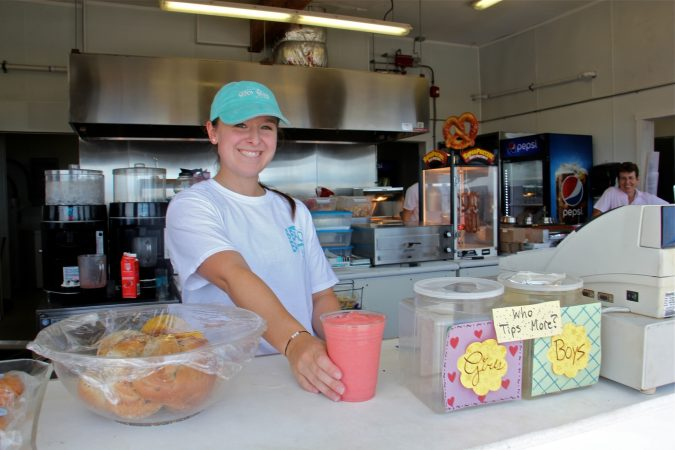 Ashley Cozzi serves up a smoothie without lid or straw at the Monmouth Beach Bathing Pavillion. (Emma Lee/WHYY)