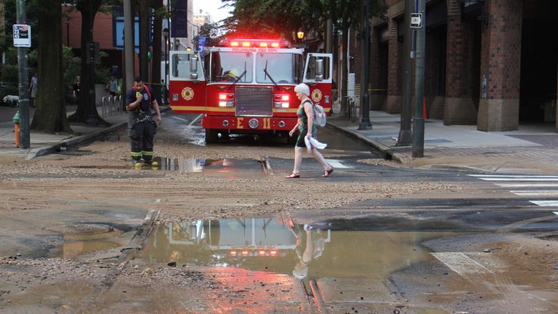A pedestrian crosses the street at 11th and Walnut streets after a water main break left Center City streets covered with water and debris. (Emma Lee/WHYY)