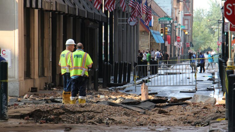 Water department employees stand at the site of the water main break at Sansom and Juniper streets. (Emma Lee/WHYY)