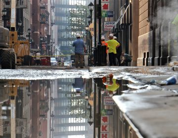 Steam pours from vents on Sansom Street near the site of a water main break that flooded Center City streets. (Emma Lee/WHYY)