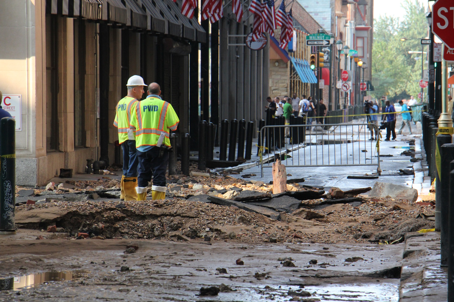 Water department employees stand at the site of the water main break at Sansom and Juniper streets.