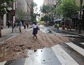 A pedestrian at Walnut and Juniper streets steps over a pile of debris left behind by a massive water main break in Center City. (Emma Lee/WHYY)