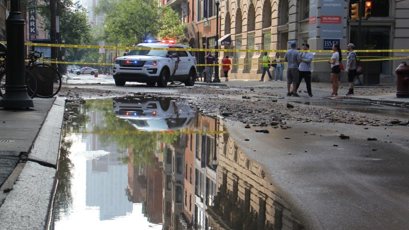 Police block traffic on Walnut Street left flooded and strewn with debris after a water main break. (Emma Lee/WHYY)