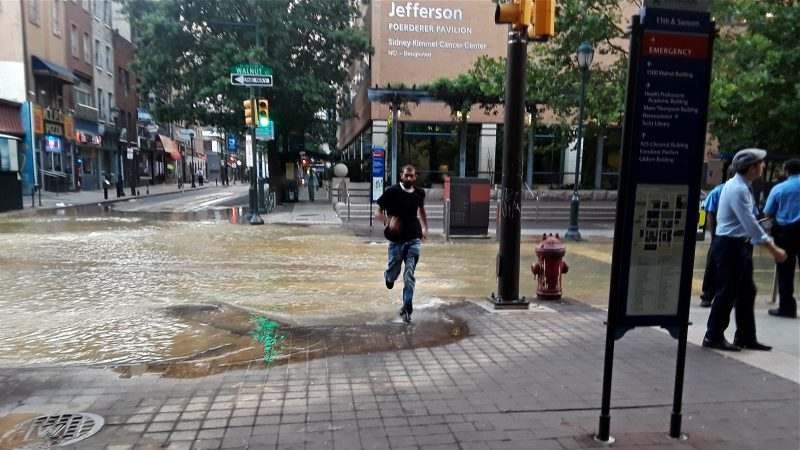 A pedestrian sprints through the flooded intersection at 11th and Walnut streets after a water main break in Center City. (Trenae Nuri/WHYY)