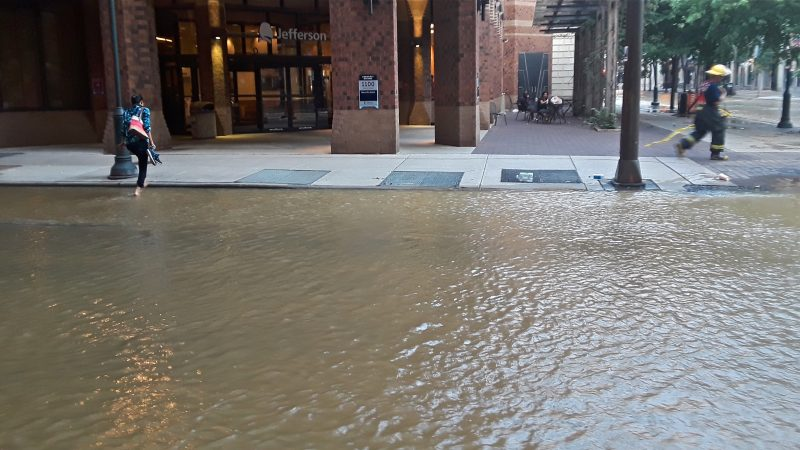 A woman took off her shoes and rolled up her pants to cross 11th street after a water main break flooded several Center City streets. (Trenae NUri/WHYY)