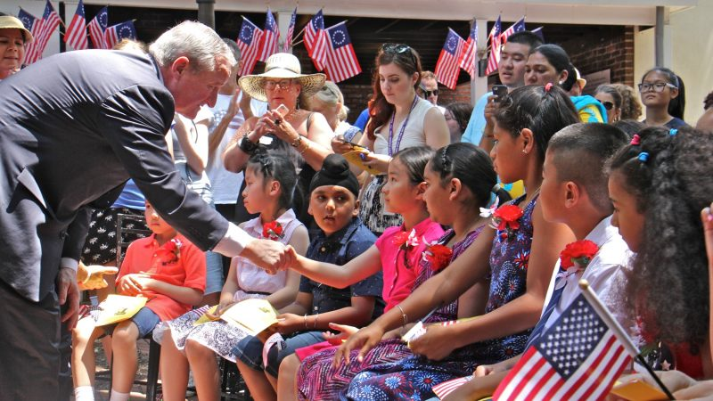 Philadelphia Mayor Jim Kenney shakes hands with each of 13 children who became U.S. citizens during a ceremony at the Betsy Ross House. (Emma Lee/WHYY)