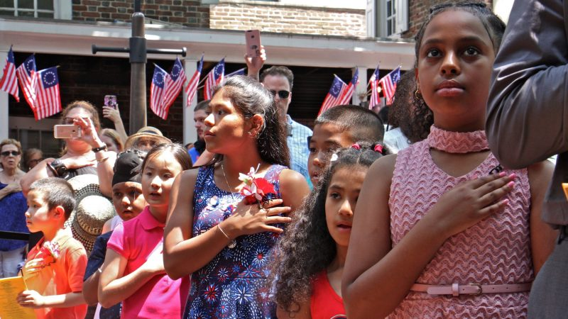 Angelica Wendel (center) of Malvern, originally from Guatemala, says the Pledge of Allegiance for the first time as a U.S. citizen. She was one of 13 children who became a U.S. citizen during a ceremony at the Betsy Ross House. (Emma Lee/WHYY)