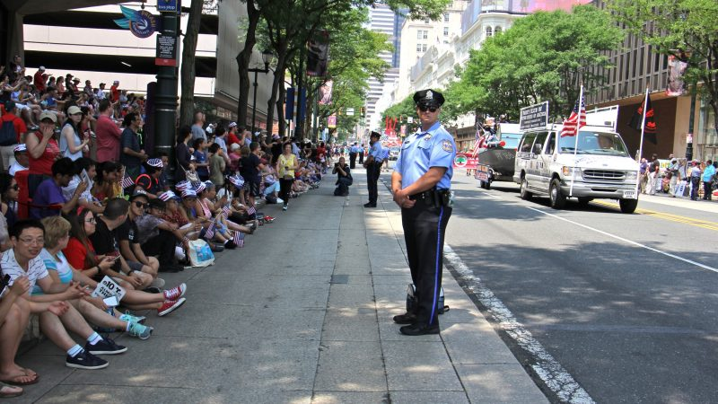 Philadelphia police stand guard along the Indepencence Day parade route on Market Street. (Emma Lee/WHYY)