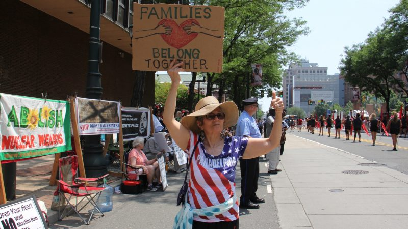 Marlena Santoyo and other protesters from the Brandywine Peace Community wave signs and banners on Market Street during the Independence Day parade. (Emma Lee/WHYY)